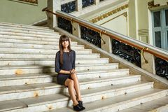 Beautiful young woman sitting on the steps stock photo