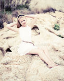 Beautiful young woman sitting on the stone Royalty Free Stock Photography