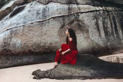 Beautiful young woman sitting on a stone on the beach at sunset Royalty Free Stock Photography