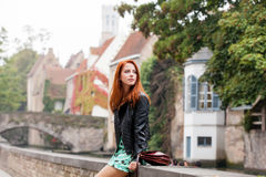 Beautiful young woman sitting on the stone fence and exploring t. He town Royalty Free Stock Photo