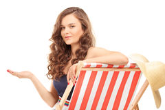 Beautiful young woman sitting on a sun lounger and gesturing wit Stock Images