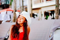 Beautiful young woman sitting on sunbed with the hat on the beach resort, summer vacation Royalty Free Stock Image