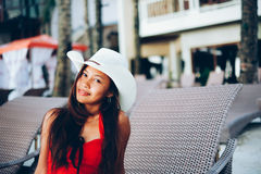 Beautiful young woman sitting on sunbed with the hat on the beach resort, summer vacation Stock Images