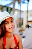 Beautiful young woman sitting on sunbed with the hat on the beach resort, summer vacation Royalty Free Stock Photos