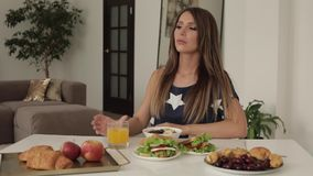 Beautiful young woman sitting on table with appetizing tasty breakfast medium shot stock video footage