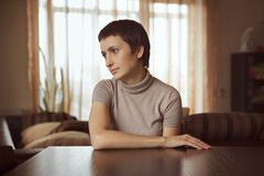 Beautiful young woman sitting at table Royalty Free Stock Images