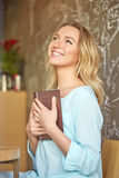 Beautiful young woman sitting at a table holding a book and dreamily looking up Stock Images