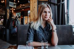 Beautiful young woman sitting at table with laptop and looking at window in cafe stock images