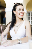 Beautiful young woman sitting at a table outdoors and drinking Royalty Free Stock Images