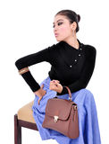 Beautiful young woman sitting with trendy bag Stock Images