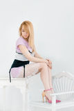 Beautiful young woman sitting in a trendy shoes royalty free stock image