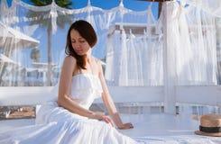 Beautiful young woman sitting under baldachin Stock Photo