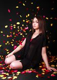Beautiful young woman sitting under the falling petals Stock Image