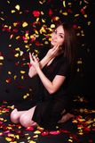 Beautiful young woman sitting under the falling petals Stock Images
