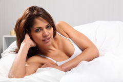 Beautiful young woman sitting up in bed Royalty Free Stock Photos