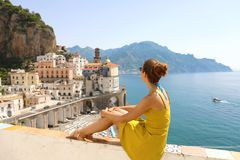 Beautiful young woman sitting on wall looking at stunning panoramic village of Atrani on Amalfi Coast, Italy.  royalty free stock photos