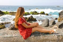 Beautiful young woman sitting on wall looking at stunning seascape in Puerto de la Cruz, Tenerife royalty free stock photo