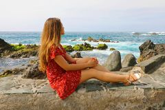 Beautiful young woman sitting on wall looking at stunning seascape in Puerto de la Cruz, Tenerife stock images