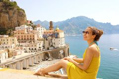 Beautiful young woman sitting on wall with panoramic view of Atrani village on Amalfi Coast, Italy stock image