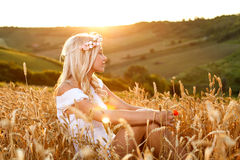 Beautiful young woman sitting in wheat at sunset Royalty Free Stock Images
