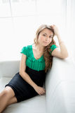 Beautiful young woman sitting on white couch next to window Stock Photography