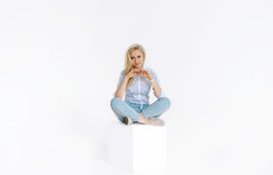 Beautiful young woman sitting on white cube in studio Royalty Free Stock Photo