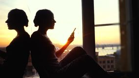 Beautiful young woman sitting on window uses smart phone drinks coffee on background of the sunset and city. 3840x2160 stock video footage