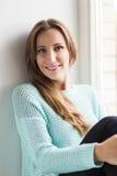 Beautiful young woman sitting on windowsill Stock Images