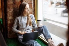 Beautiful young woman sitting on windowsill and using laptop stock photo