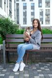 Beautiful young woman sitting on wooden bench and enjoy with her cute little husky puppy Stock Photography