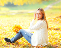 Beautiful young woman sitting with yellow maple leafs in warm sunny autumn Stock Images