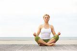 Beautiful young woman sitting in yoga pose at the beach Royalty Free Stock Images