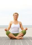 Beautiful young woman sitting in yoga pose outdoors Stock Photos