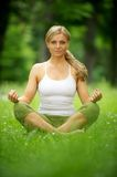Beautiful young woman sitting in yoga position in the park Royalty Free Stock Photos