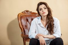 Beautiful young woman is situated on chair royalty free stock image