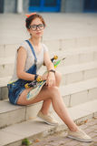 Beautiful young woman with skateboard in city Stock Photography