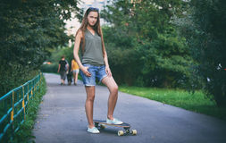 Beautiful young woman with skateboard Stock Photo