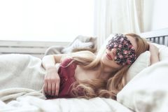 Beautiful young woman sleeping in her bed at home with blindfold eye mask. Royalty Free Stock Image