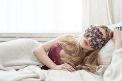 Beautiful young woman sleeping in her bed at home with blindfold eye mask. royalty free stock images