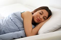 Beautiful young woman sleeping while lying in bed comfortably and blissfully.  Royalty Free Stock Photography