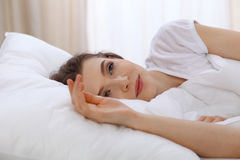 Beautiful young woman sleeping while lying in bed comfortably and blissfully. Early morning, you wake up for work or the Stock Image