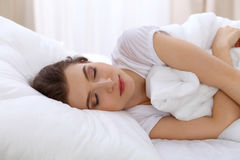 Beautiful young woman sleeping while lying in bed comfortably and blissfully. Early morning, you wake up for work or the. Day off concept Stock Photography