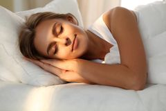 Beautiful young woman sleeping while lying in bed comfortably and blissfully. Sunbeam dawn on her face.  Stock Photo