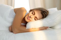 Beautiful young woman sleeping while lying in bed comfortably and blissfully Sunbeam dawn on her face.  stock photo