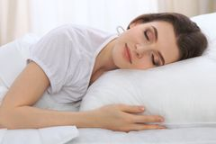 Beautiful young woman sleeping while lying in her bed and relaxing comfortably. It is easy to wake up for work or the. Day off. Concept of pleasant and rest Royalty Free Stock Images