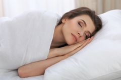 Beautiful young woman sleeping while lying in her bed and relaxing comfortably. It is easy to wake up for work or the. Day off. Concept of pleasant and rest Royalty Free Stock Photos