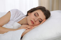 Beautiful young woman sleeping while lying in her bed and relaxing comfortably. It is easy to wake up for work or the Stock Photos