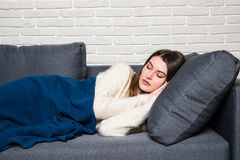 Beautiful young woman is sleeping and seeing sweet dreams on sofa at home royalty free stock image