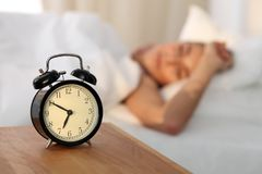 Beautiful young woman sleeping and smiling while lying in bed comfortably and blissfully on the background of alarm. Clock is going to ring. Sunbeam dawn on her Royalty Free Stock Images