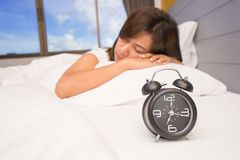 Beautiful young woman sleeping and smiling while lying in bed comfortably and blissfully on the background of alarm clock stock images
